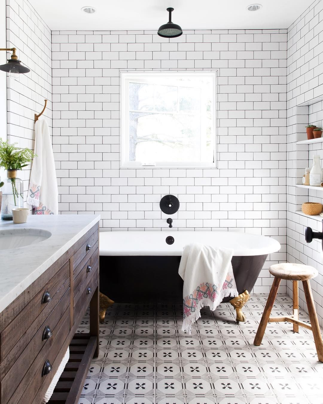 Subway tile bathroom with patterned tile floor and black clawfoot ...