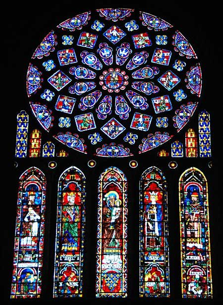 """The North Rose (probably the best known of all the great rose windows of the cathedrals of Northern France) and Lancet Windows over the North Portal. The windows were given to the Cathedral in 1230 by Queen Blanche of Castile (grand-daughter of Eleanor of Aquitaine, and Queen Consort of French King Louis VIII """"The Lion"""" and subduer of Cathars)."""