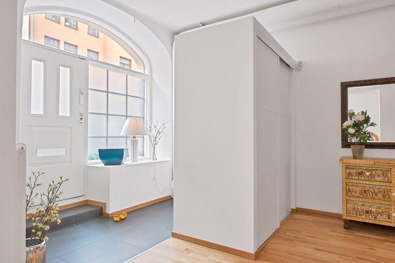 Harmaa lattia, puulattialista, valkoiset seinät. Kaunisti ajateltu, että puulattialista on yhteneväinen sitten muun huoneiston osan kanssa.