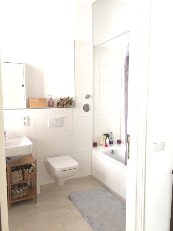 Helles, modernes Badezimmer mit grauem Teppich und weißen Fliesen