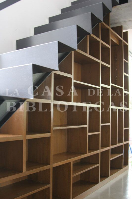 biblioteca moderna bajo escalera realizada en madera para