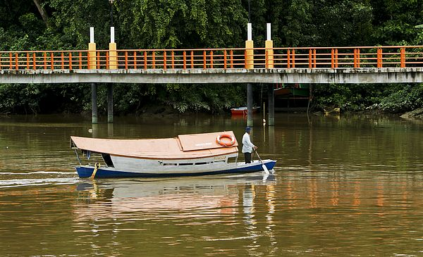 A boat taxi slowly crosses the river in Kuching, Malaysia on the Island of Borneo during the early morning hours