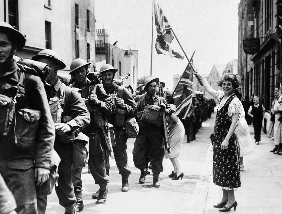 31 Women waving Union Jacks greet passing soldiers, all Canadians, as they march from the docks after disembarking in France on June 18, 1940. (AP Photo) #