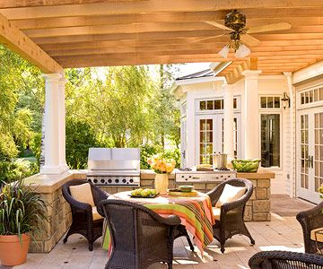 Great outdoor kitchen with a large stainless-steel grill and comfy furnishings.