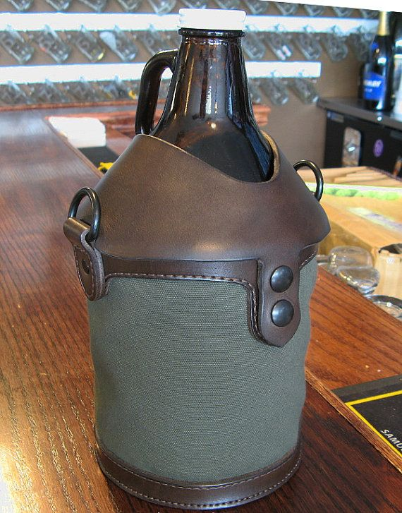 Canvas and leather beer growler carrying case in green OD canvas with matching adjustable web strap.