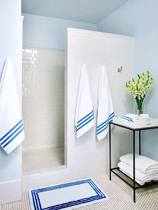 Classic white subway tiles cover the shower walls and help to brighten the room. The homeowners kept the white hexagonal floor tiles to enhance the room's old-fashioned aesthetic.