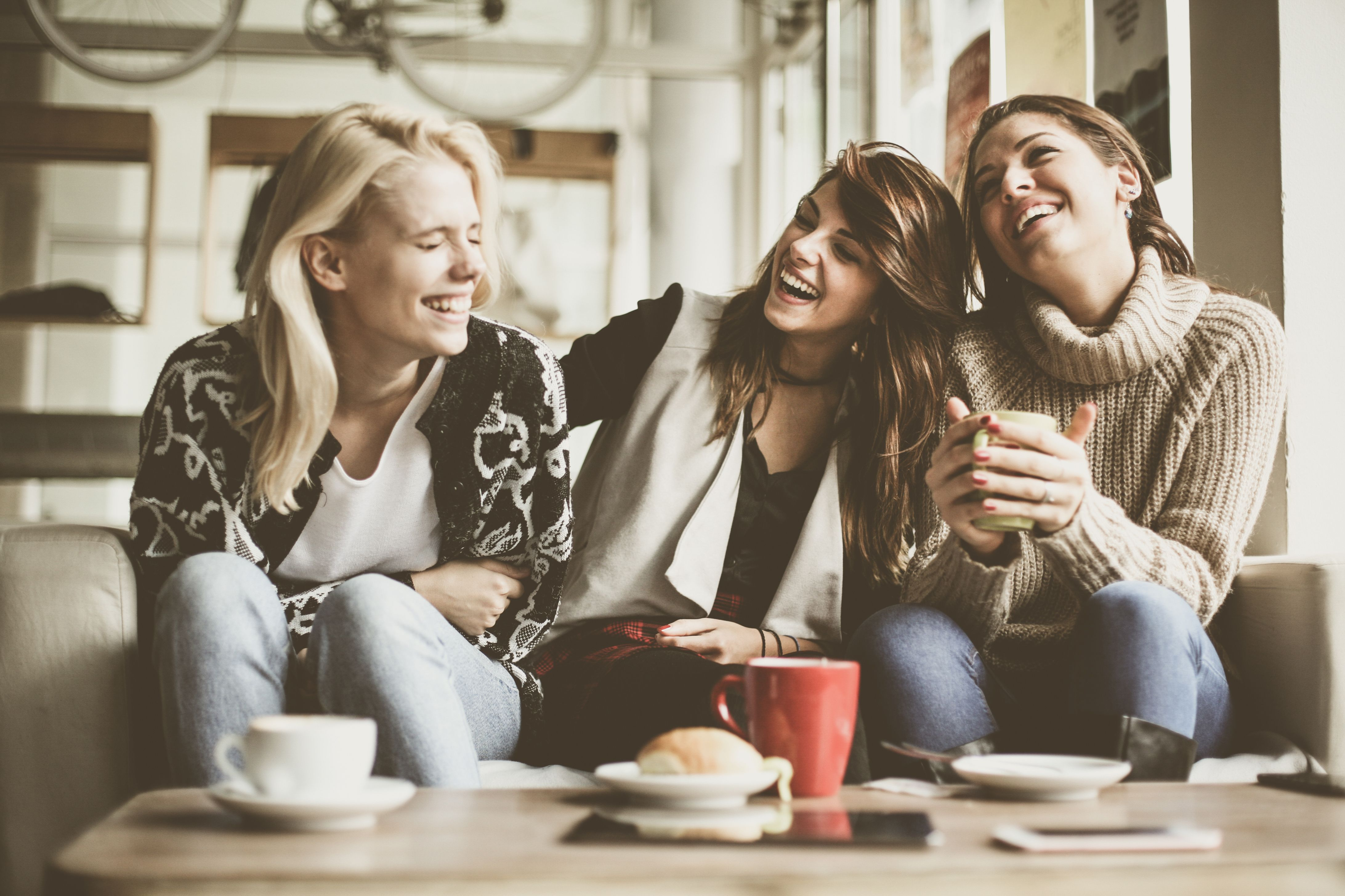 Three women laughing in a cafe