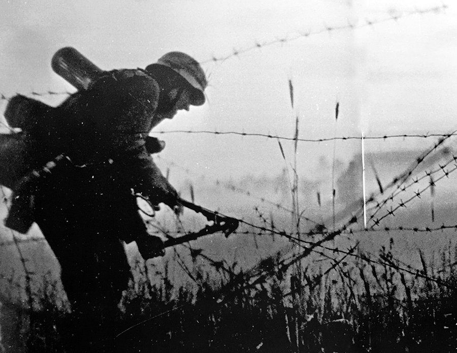 A German soldier cuts through barbed wire at the border of the ...