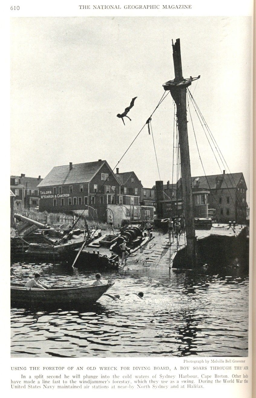 boy diving from the foretop of an old wreck into the harbour in