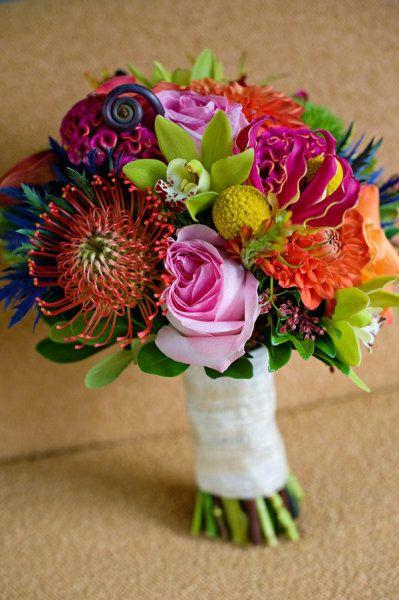Funky colorful combination of green cymbidium orchids, orange pin cushions, lt. pink roses, orange dahalias, fern curls, fuchsia celosia - so fun!