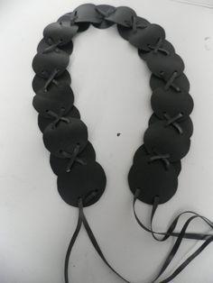 Zwarte riem. Een riem bestaande uit cirkels.De cirkels worden bijeengehouden door 2 veter gekruist.Het is gemaakt van autoband. Het is sterk