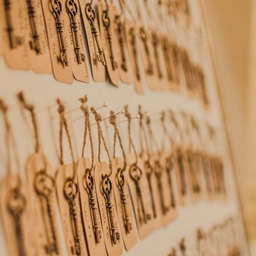 Guests found their names on luggage tags attached to unique brass skeleton keys. They went perfectly with the upholstered corkboard framed seating chart.   Photo Credit: Mary Sarah Photography