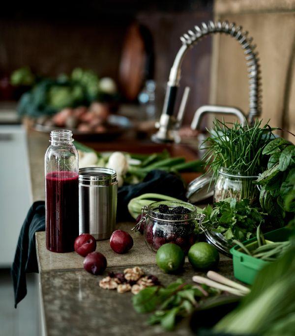 Työtasolla lasipurkkeja, termoskannuja ja pullo, jotka ovat täynnä marjoja ja punaista hedelmämehua.