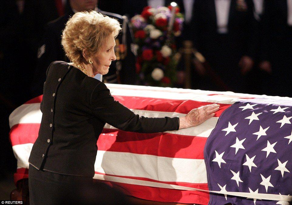 Nancy Reagan raakt de kist van haar man, de voormalige Amerikaanse president Ronald Reagan, want het ligt opgebaard in de rotonde van de Verenigde Staten Capitool in Washington, 9 juni 2004