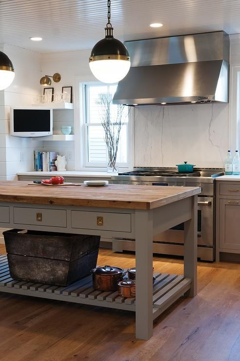 A pair of Hicks Pendants hang over a freestanding gray kitchen island fitted with drawers adorned with unlacquered brass vintage hardware topped with butcher block.