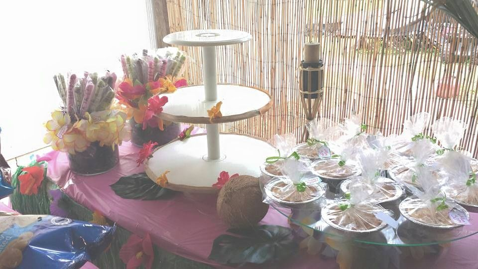 Partially filled dessert table. Mini lemon and coco cheesecakes and chocolate dipped pretzels. Cupcakes and cake to be put on decorated cake stand.