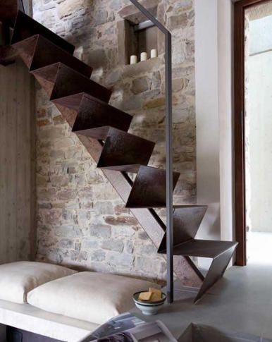 Pared de piedra con banco bajo escalera de hierro escaleras