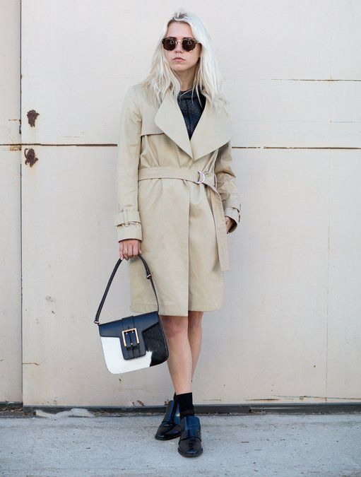 Always Judging wears a beige trench coat and accessories with sunglasses and a white and black bag | Fashiolista.com
