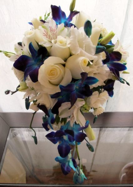 Cascade Of White Roses Alstroemeria Lisianthus And Blue Dendrobium Orchids Beach Wedding Centerpieces Flowers Beach Wedding Flowers White Wedding Bouquets