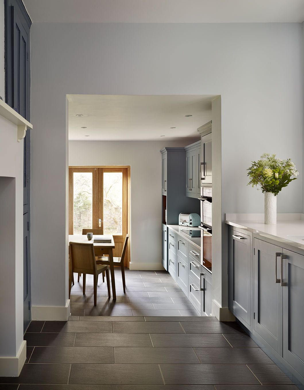 Hand-painted, dark blue cabinets have been paired with ...