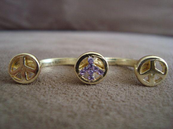 """Anel duplo em metal dourado com o símbolo """"Paz e Amor"""". Aplicação de strass Swarovski lilás no meio.  Aros 13 (diâmetro 1,6cm) e 14 (diâmetro 1,61cm) R$30,00"""