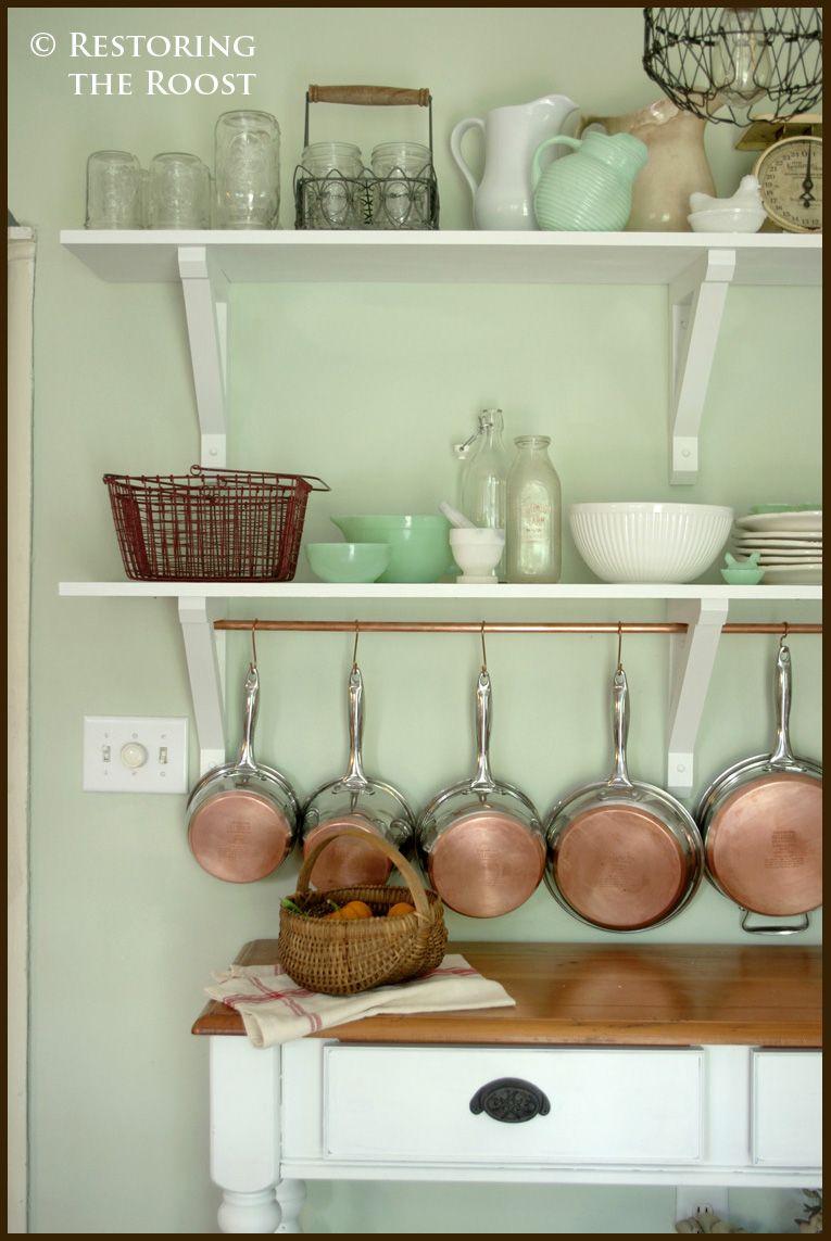 White shelves on a seafoam wall.