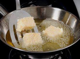 Aperitivo de mandioca: Conclusão - Forre uma forma com papel filme, despeje a massa e resfrie até conseguir consistência para cortar em cubos na própria forma. Leve ao freezer por duas horas, sem tirar os cubos da forma. Frite na hora de servir.