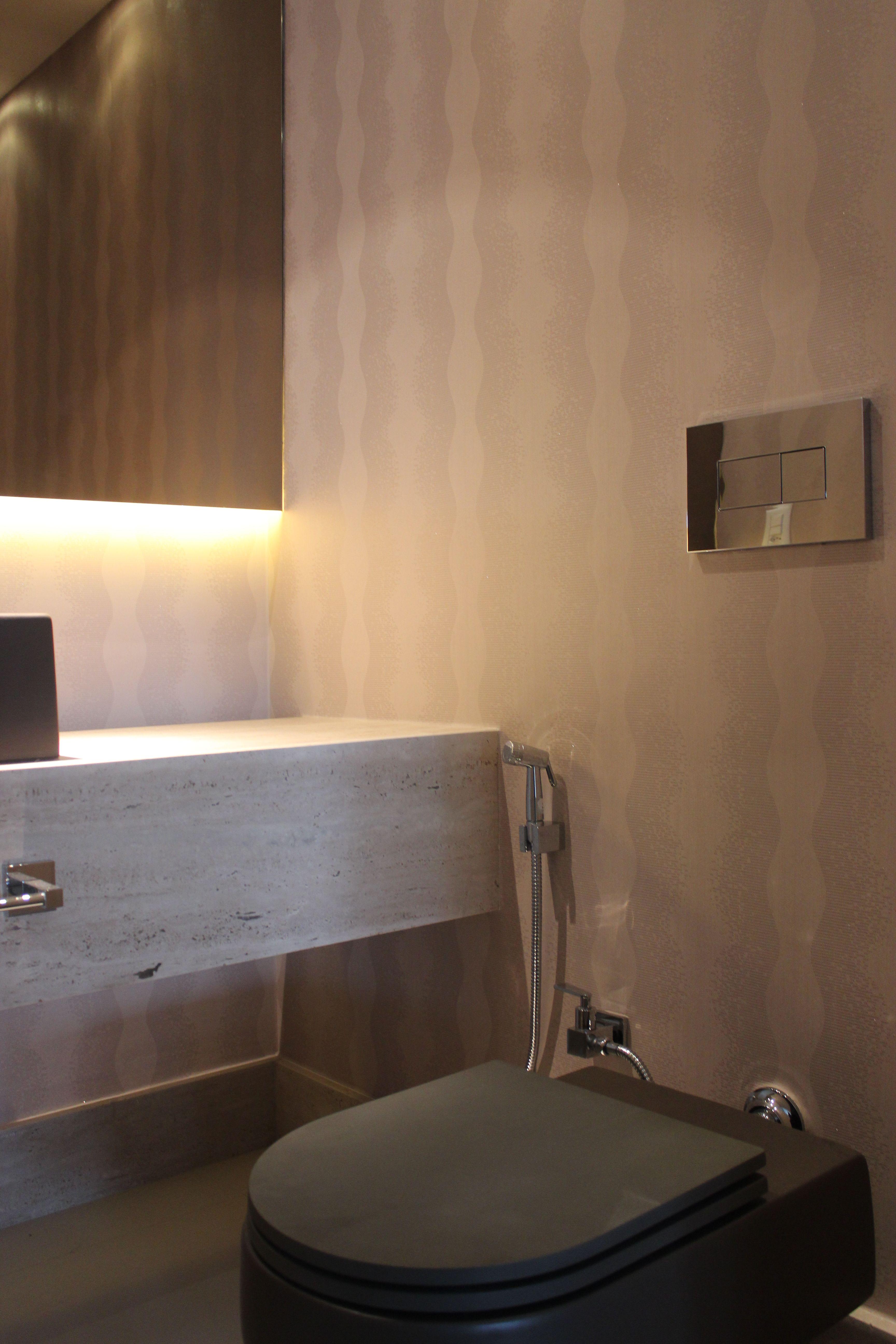 Lavabo com bancada em Travertino Bruto e espelho bronze iluminado.