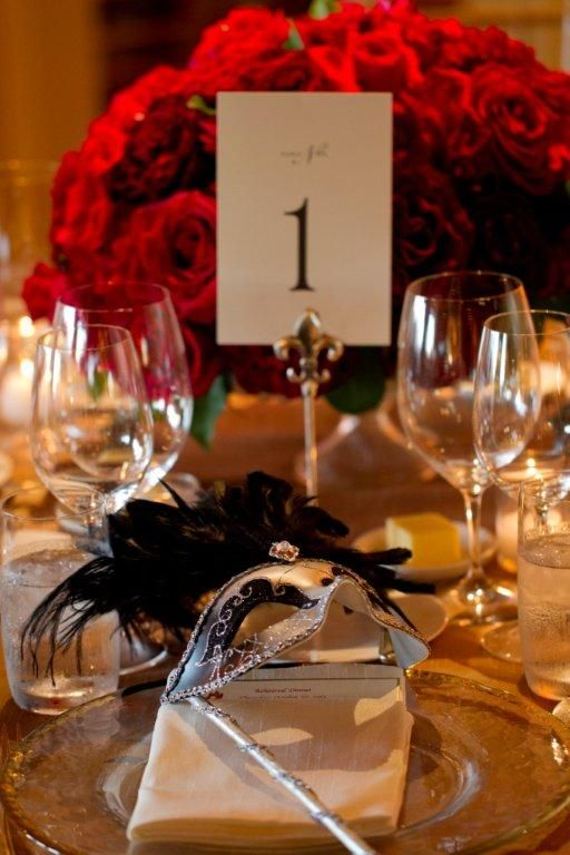 Red roses for a centerpiece and a gorgeous masquerade theme gives a creative spin on a table top design. Masquerade masks placed on a glass charger is a dramatic California Wine Country wedding.