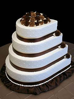 Unusually Shaped White And Brown Wedding Cake In A Teardrop Shape Decorated With Satin
