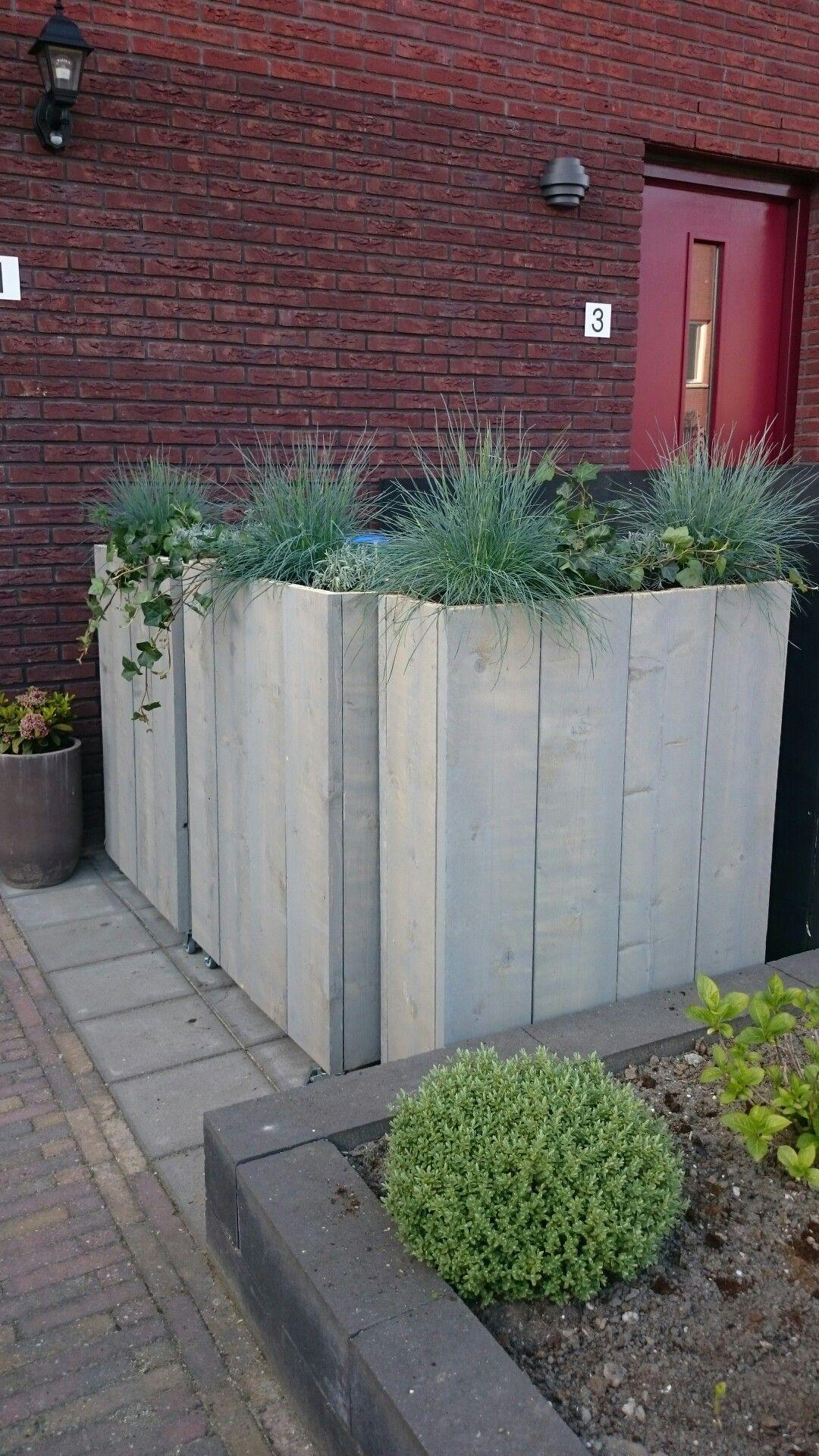 Hoge verrijdbare plantenbakken als afscheiding voor de containers