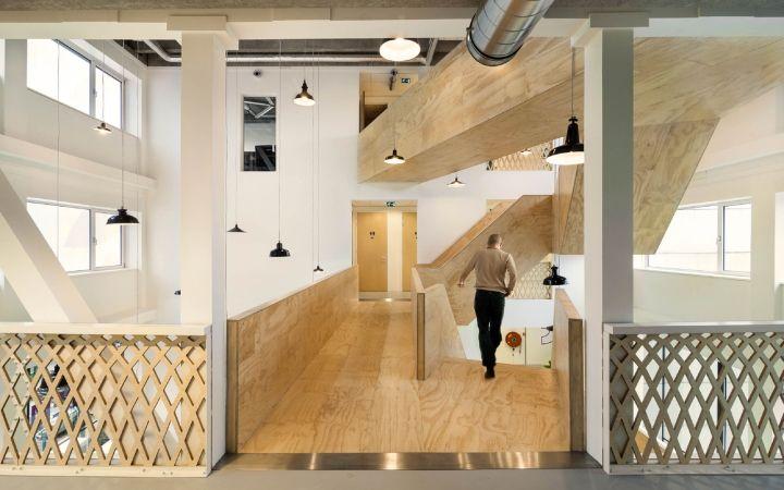 Дизайн офиса в светлых тонах с древесной лестницей от Studioninedots