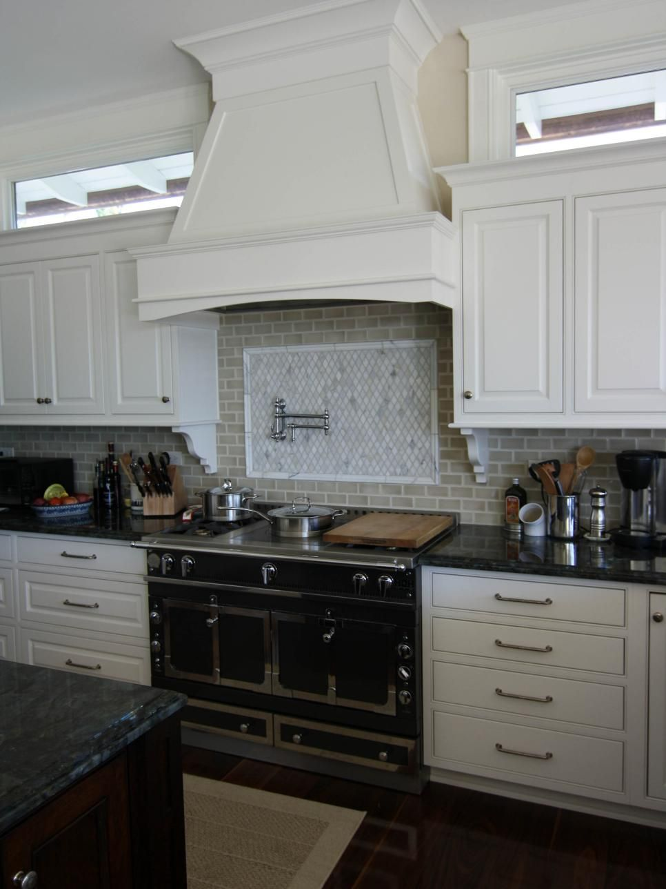 White cabinetry complements the dark granite countertops ...