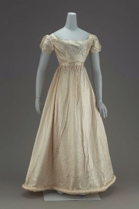Woman's dress of white satin        English or American, 1817         England or U.S.A.  Dimensions      128 x 107 cm (50 3/8 x 42 1/8 in.) measured flat for flat storage, width due to deeply padded hem. L. around waist band .588  Medium or Technique      Silk satin, cotton plain weave, wool batting, metal hook and eye closures  Classification      Costumes     Accession Number      44.11  Not on view