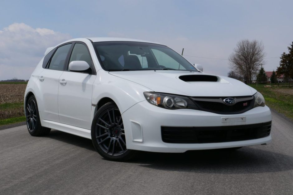 This 2010 Subaru Impreza WRX STi is one of 125 Special Edition cars produced for the US market in 2010 and is finished in Aspen White. The car originally resided in New York and was acquired by the selling dealer in a 2020 BaT auction. The turbocharged 2.5L flat-four is paired with a six-speed manual transmission, and power is sent to all four wheels via an electronically controlled center differential and front and rear limited-slip differentials. The Special Edition STi included a thicker rear