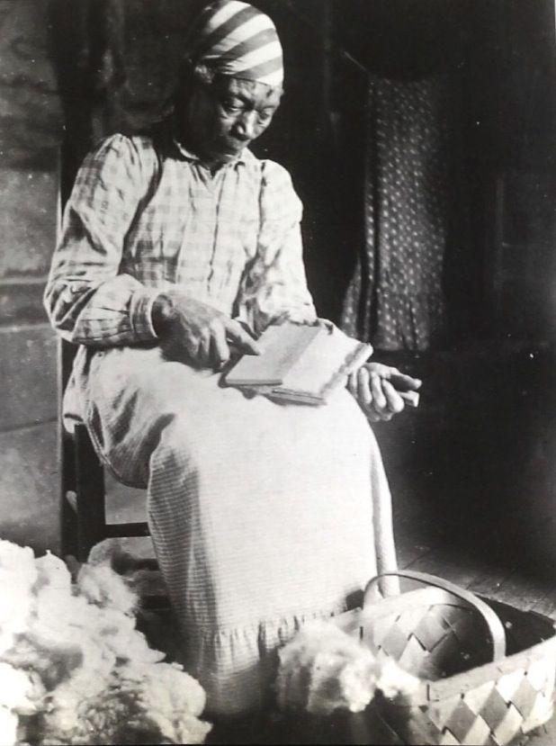 From The Face of Our Past: Images of Black Women from Colonial America to Present. Editors Kathleen Thompson and Hillary Mae Austin (1999) page 46. Aunt Ca'ine carding fiber, most likely cotton, on the Rosemary Plantation.