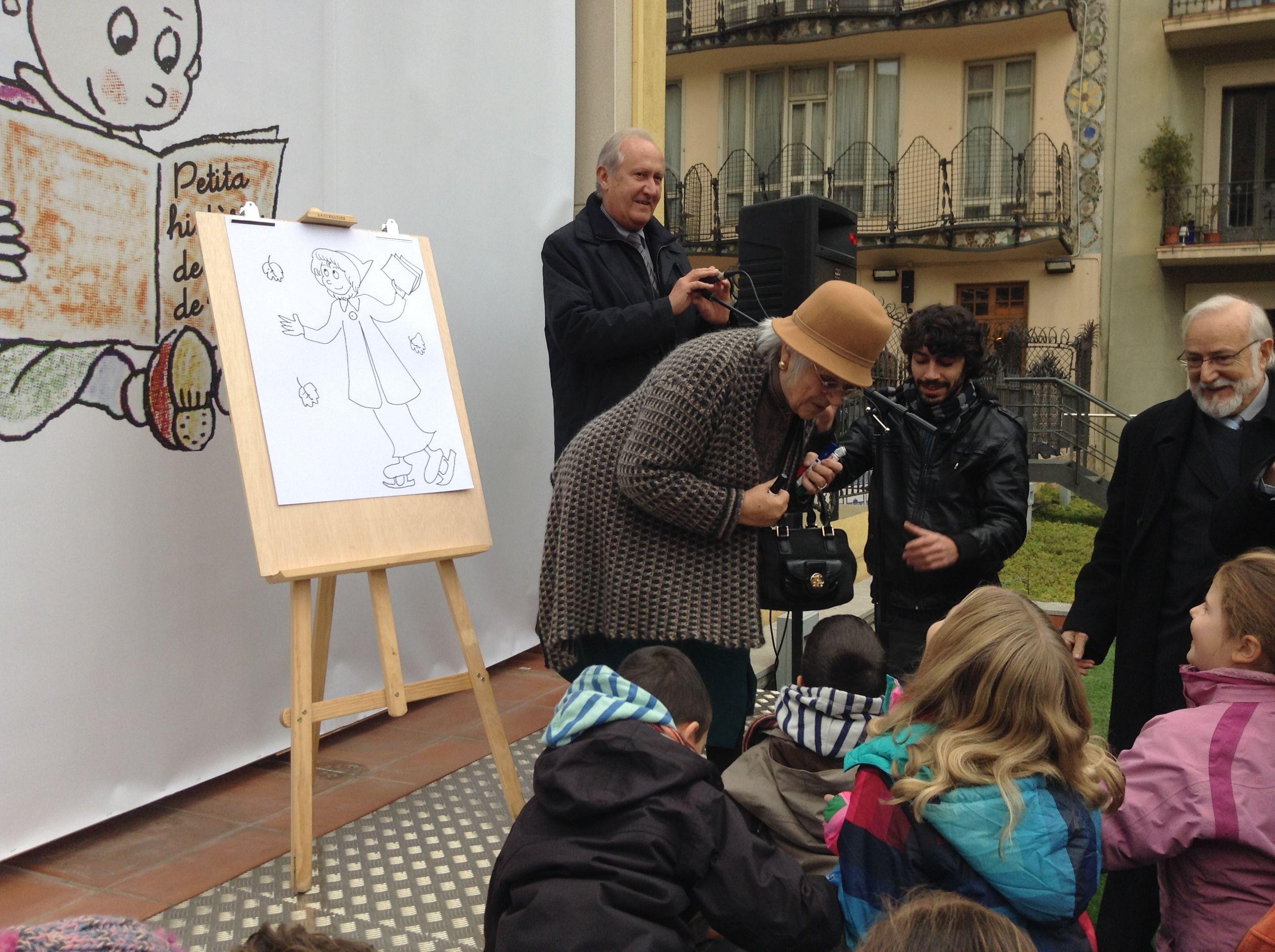 Pilarín Bayés parla amb els lectors més joves després de fer un dibuix.
