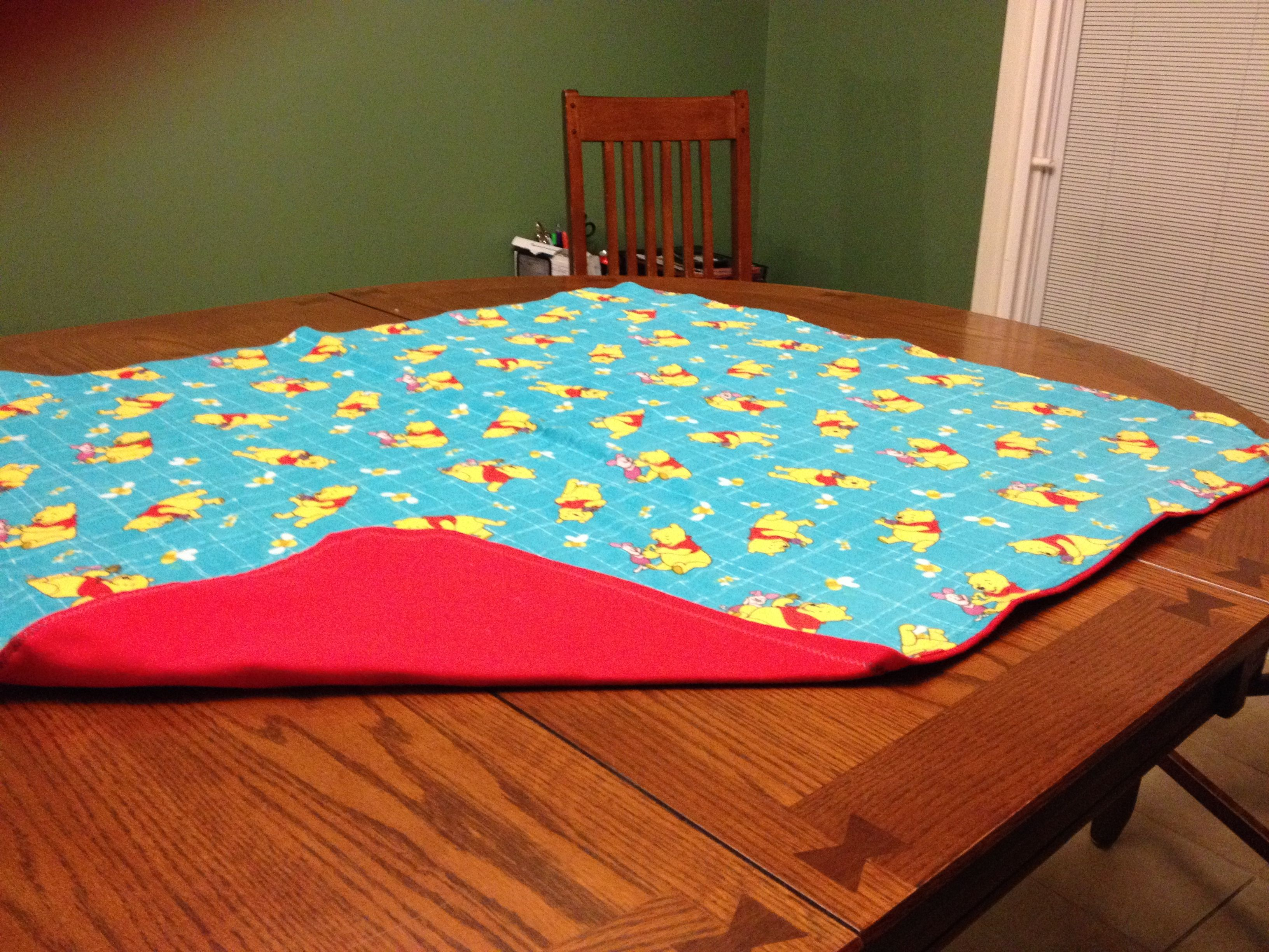 PRICE: $25.00. Flannel Winnie the Pooh blanket with red backing measures 40in  X 35in MADE BY KRIS