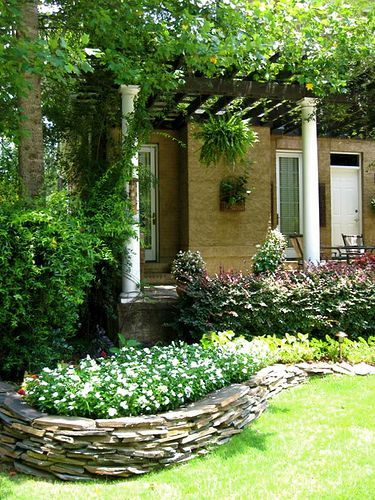 Terraced bed | Stone landscaping, Stone flower beds ...