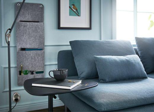 Ein Wohnzimmer mit Sofa, Standleuchte, Hängeorganisation und