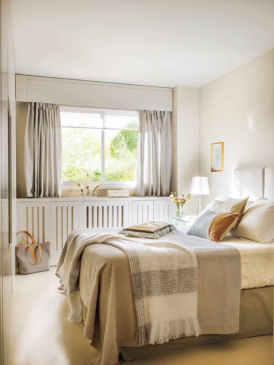 Dormitorio en tonos claros con un mueble bajo la ventana y ropa de ...