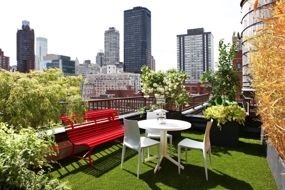 The grass flooring and multitude of plant life make this veranda feel more connected to the outdoors among a city full of sky scrappers. It remains simple and modern with red and white furnishing.