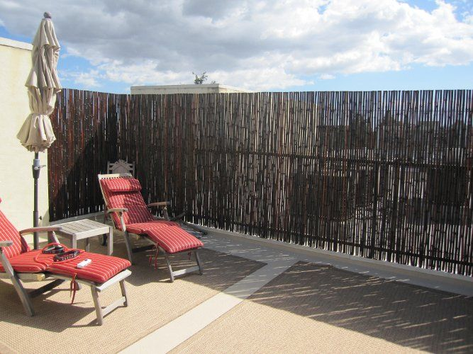 Superb A Perfect Rooftop Oasis With Black Bamboo Fence.