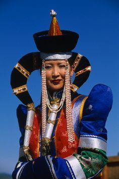 """Sheephorn"" headdress (Mongolia)- This is created by stiffening and shaping the hair with congealed mutton fat and then holding it in place with colored clips."