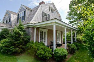 Covered Gambrel Porch With Brick Patio Has French Doors