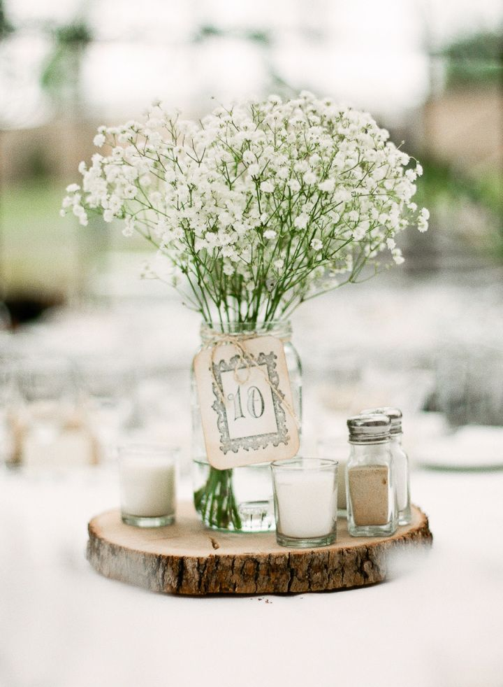 mason jar filled in baby's breath and candles on wood slice #centerpieces #masonjars #weddingcenterpieces