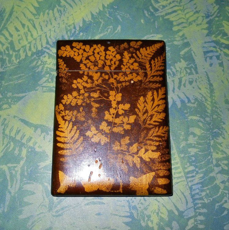 English Fern wood card case circa 1870. These were souvenirs from the Isle of Arron. Craftsmen used pressed ferns and stenciled around them with a darker brown on light sycamore wood.   When dried the ferns were removed.  Judith Walker's Collection