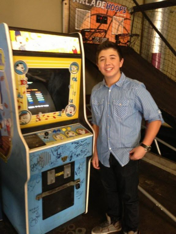 "Bradley Steven Perry Standing By Disney's ""Wreck-It Ralph"" Based Arcade Game Machine"