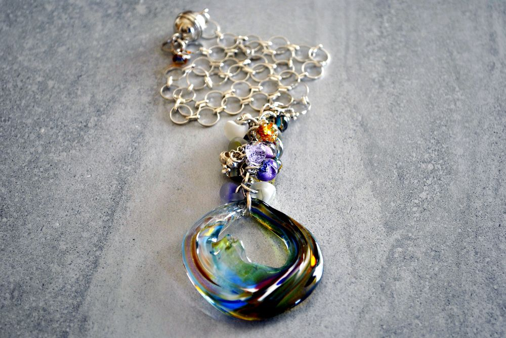 Recycled art glass that has been flame-worked and hand sculpted. A silver-plated chain above a gorgeous art glass disc with endless swirling jewel tones.