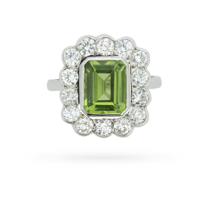 So classic, you'd never guess that this beautiful peridot and diamond halo ring was made in the 1980s! The ring is set at centre with a 2.60 carat emerald cut peridot embellished at its outer edge by a single row of well-matched round brilliant cut diamonds weighing 1.40 carats, all in a pretty 18 carat …